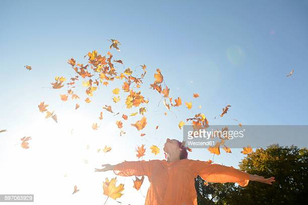 Young woman throwing autum leaves in the air