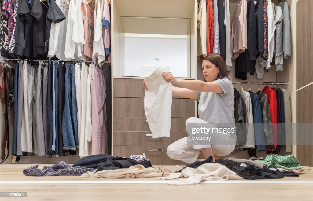 Young woman throwing clothes in walk in closet. Mess in wardrobe and dressing room : Stock Photo