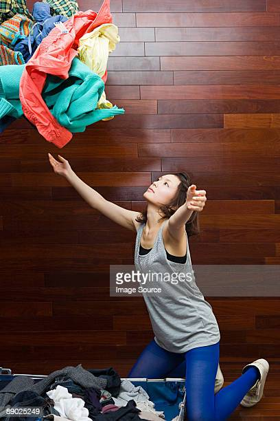 Young woman throwing clothes
