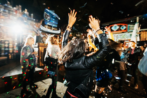 Young Woman Throwing Hands In Air While Dancing At Open Air Nightclub - gettyimageskorea