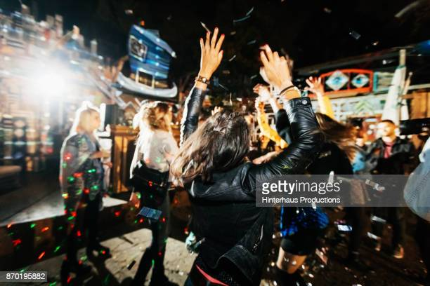 young woman throwing hands in air while dancing at open air nightclub - dancing stockfoto's en -beelden