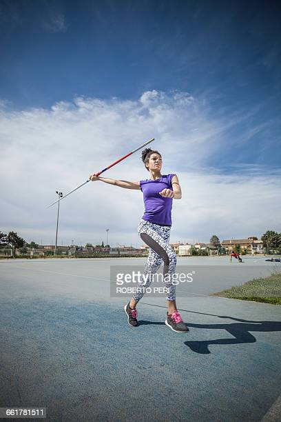 young woman throwing javelin in sports ground - javelin stock pictures, royalty-free photos & images