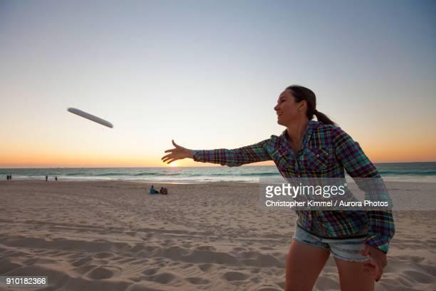 Young woman throwing plastic ring on beach, Perth, Western Australia, Australia