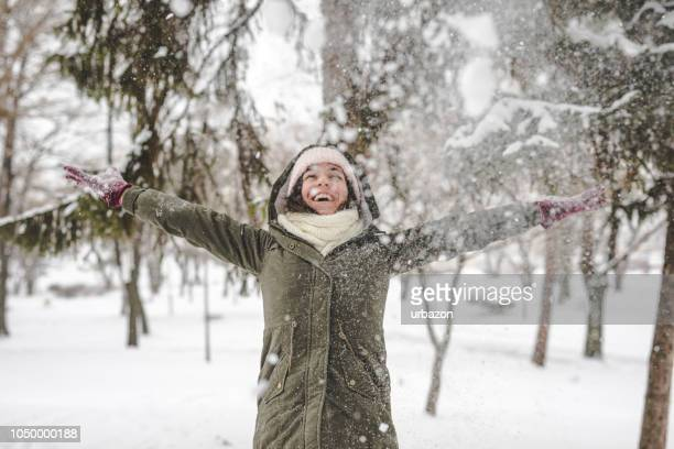 young woman throwing snow - february stock pictures, royalty-free photos & images
