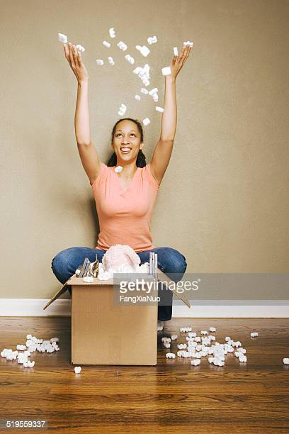 jeune femme jeter de mousse de polystyrène dans l'air - demenagement humour photos et images de collection