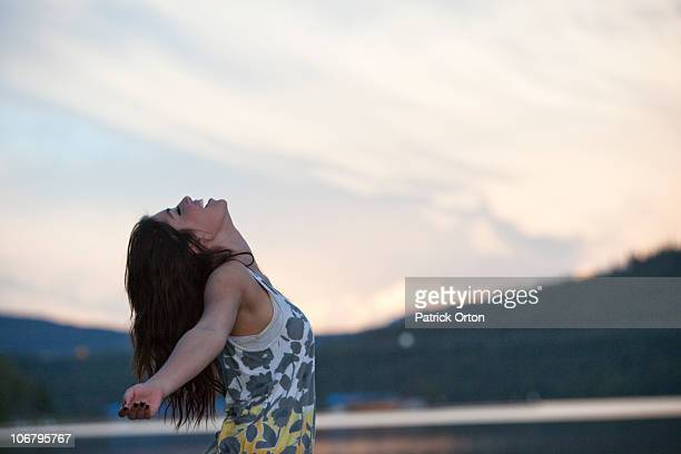 Young woman throws her head back at sunset next to the lake.