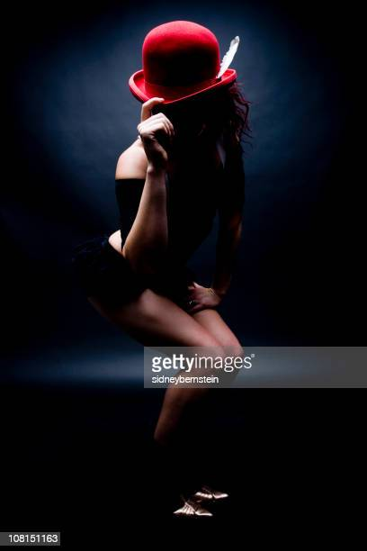 young woman tipping red bowler hat, low key - cabaret stock pictures, royalty-free photos & images
