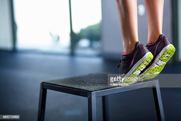Young woman tiptoeing on edge of stool
