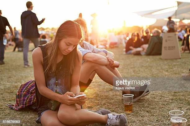 Young woman tjecking smartphone at festival