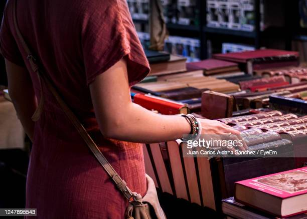 young woman toiching some books while deciding which to buy in a local street bookstore - street market stock pictures, royalty-free photos & images