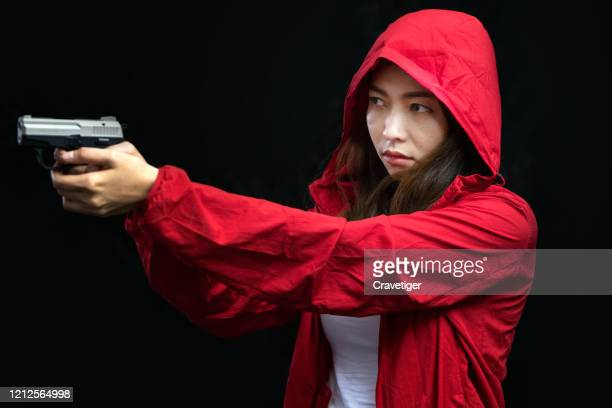 young woman took aim with pistol . criminal in control. - murderer stock pictures, royalty-free photos & images