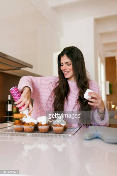 Young woman topping cup cakes with whipped cream
