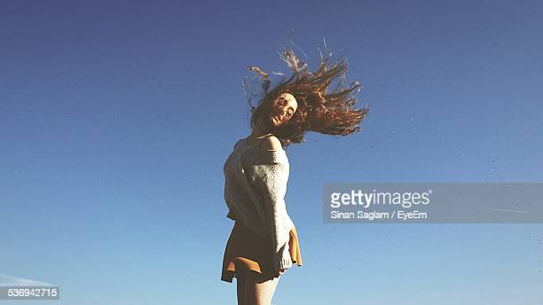 Young Woman Tossing Hair Against Clear Blue Sky