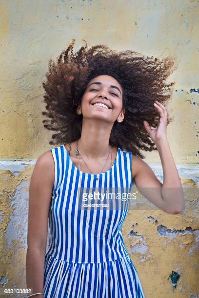young woman tossing hair against weathered wall - striped dress stock photos and pictures