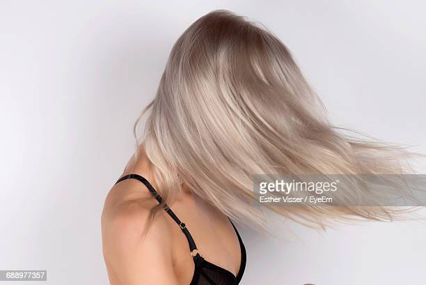 Young Woman Tossing Hair Against White Background