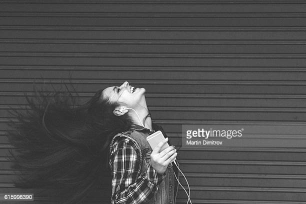 Young woman tossing hair and enjoying the music