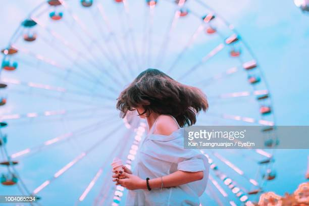 young woman tossing hair at amusement park - 観覧車 ストックフォトと画像