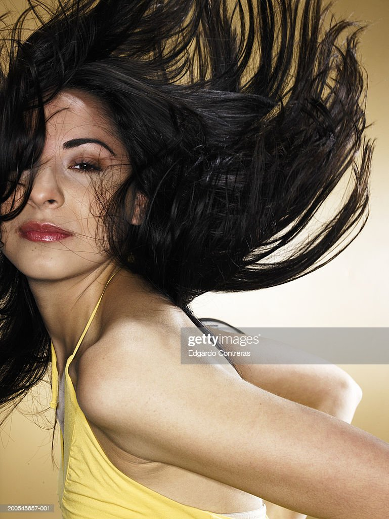 Young woman tossing hair, portrait : Stock Photo