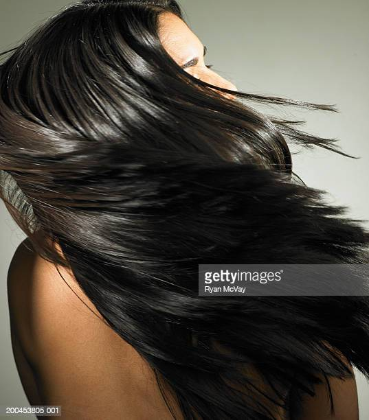 Young woman tossing hair, rear view