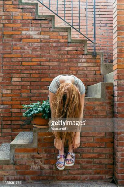 young woman tossing hair while sitting on staircase - inclinar se pose imagens e fotografias de stock