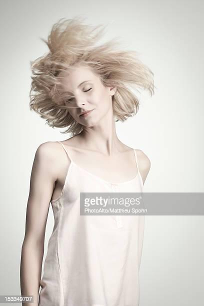 young woman tossing hair with eyes closed - cami fotografías e imágenes de stock