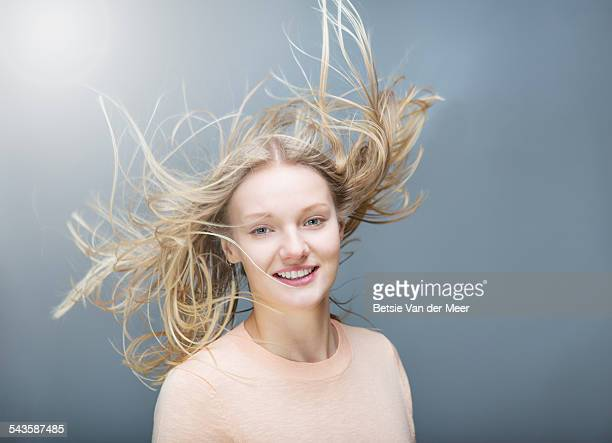 young woman tossing her  flowing long hair - vento foto e immagini stock