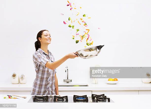 Young woman tossing vegetables in wok