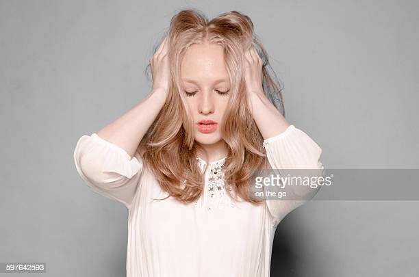 Young Woman touches her hair and closes her eyes