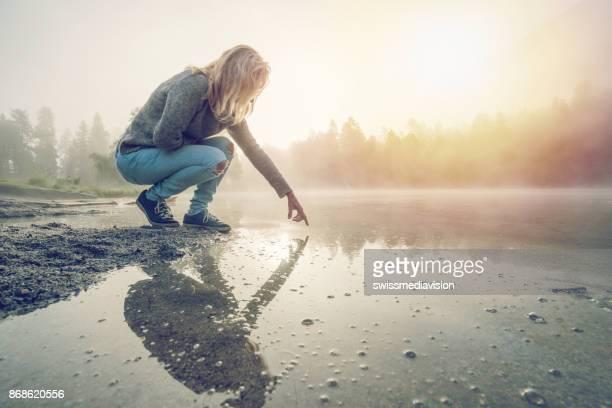 jonge vrouw raakt oppervlak van bergmeer, zwitserland - weerkaatsing stockfoto's en -beelden