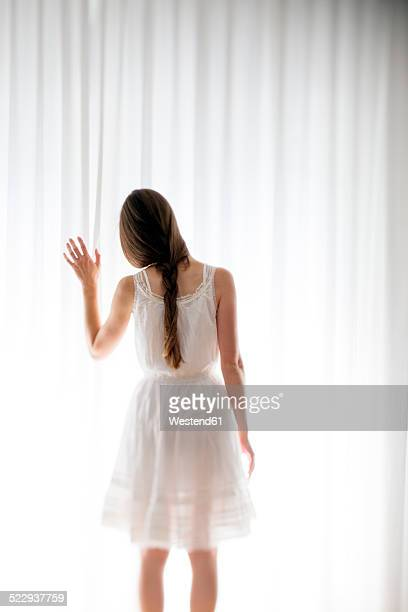 Young woman touching a white curtain, back view