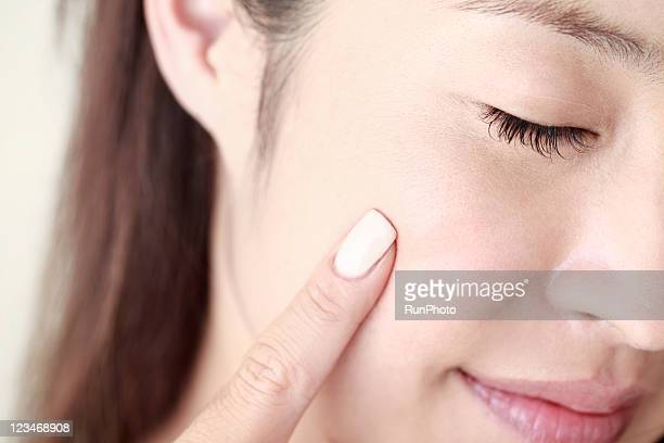 young woman touching blush,close-up,beauty care