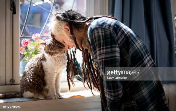 young woman touching cat with her head - north holland stock pictures, royalty-free photos & images