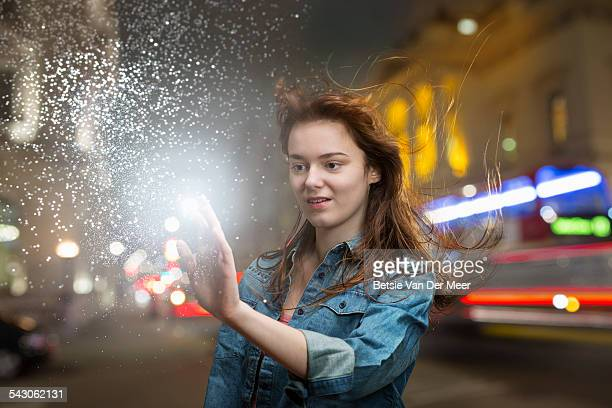 Young woman touching energy source on urban street