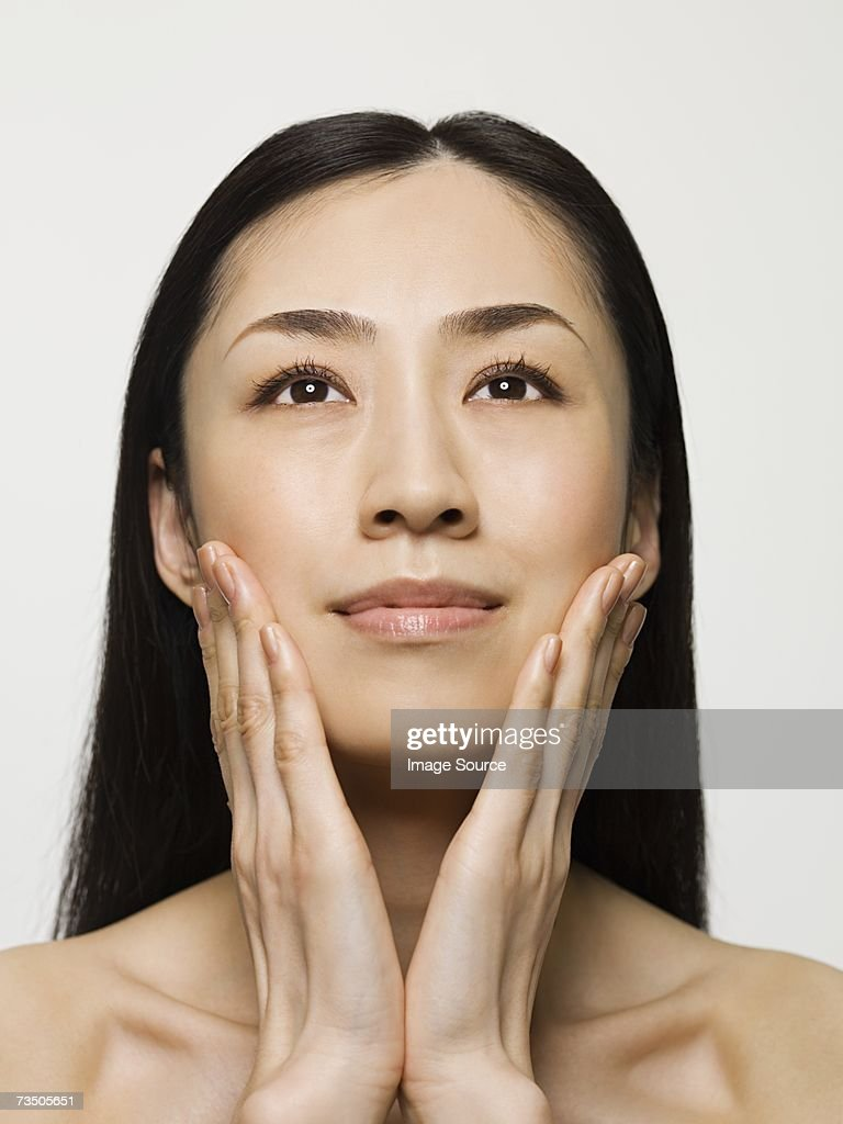Young woman touching face : Stock Photo