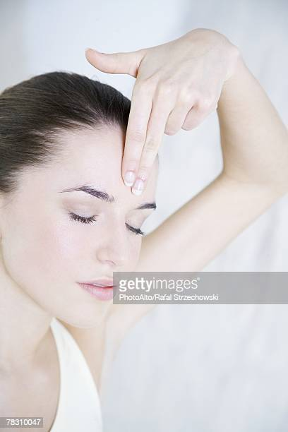 Young woman touching forehead, eyes closed