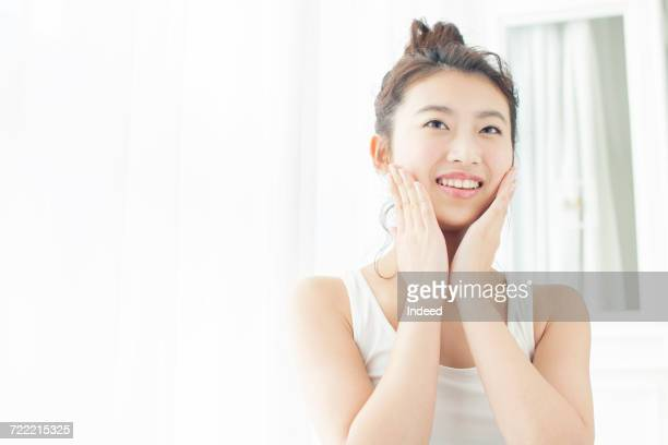 young woman touching her cheek, smiling - 人の肌 ストックフォトと画像