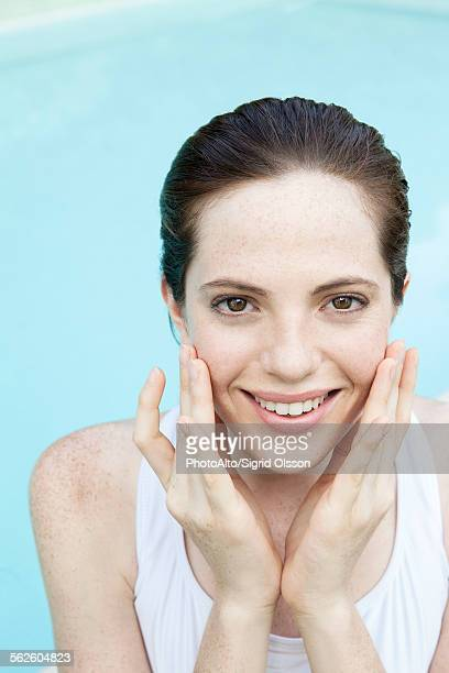 Young woman touching her cheeks, smiling cheerfully, portrait