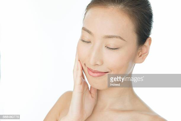 Young woman touching her face, eyes closed