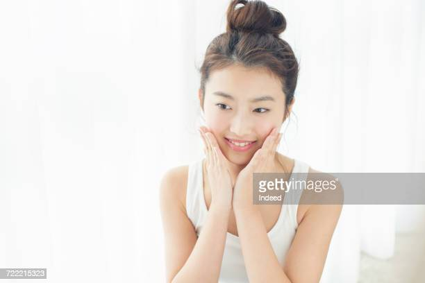 Young woman touching her face skin, smiling