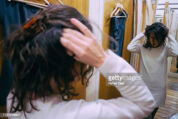Young woman touching her hair and looking at the mirror in the changing room