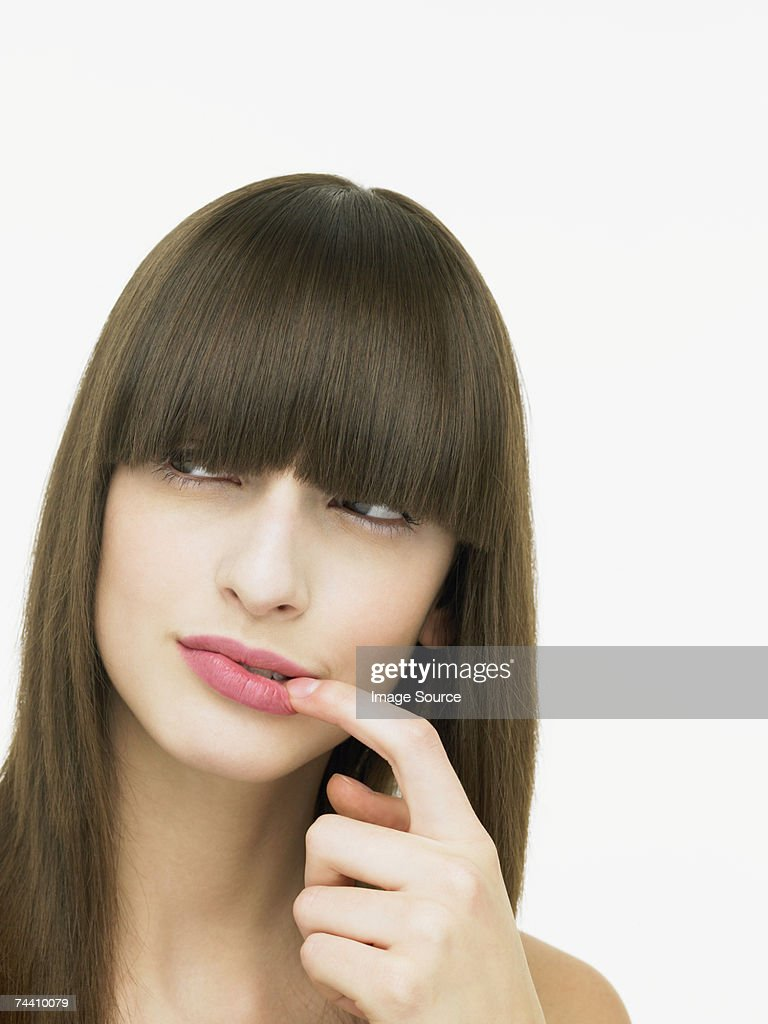 Young woman touching her lip : Stock Photo