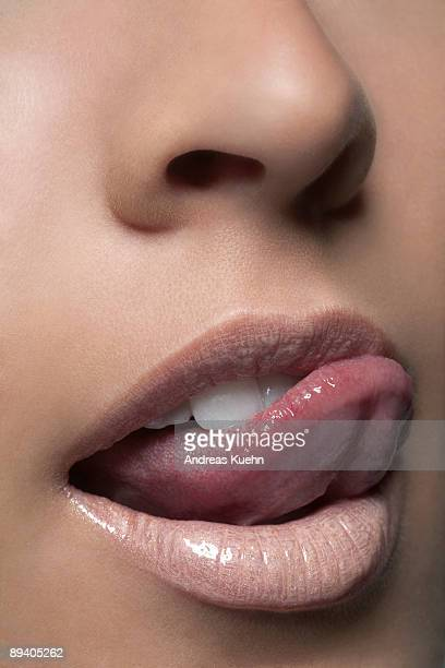 young woman touching lip with tongue, close up. - desire stock pictures, royalty-free photos & images