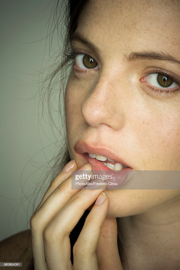 Young woman touching lips nervously, portrait : Stock Photo