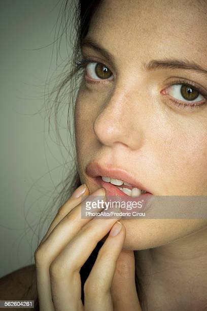 Young woman touching lips nervously, portrait