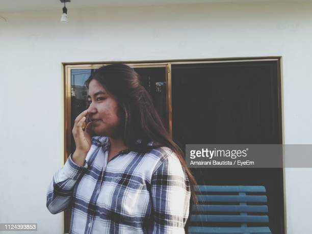 Young Woman Touching Nose While Standing Against Wall At Home
