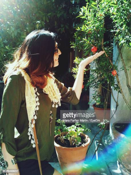 Young Woman Touching Plants During Sunny Day
