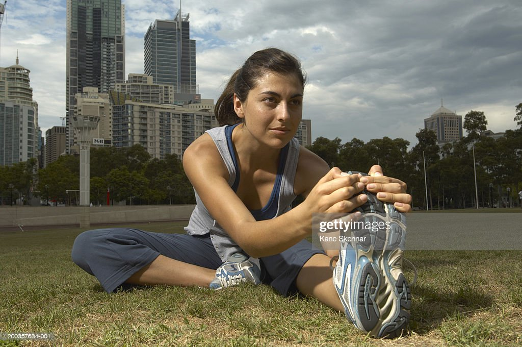 Young woman touching toes, close up : Stock Photo