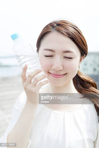 Young woman touching water bottle on her cheek