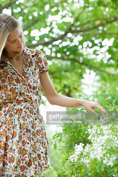 young woman touching wildflowers - robe à motif floral photos et images de collection