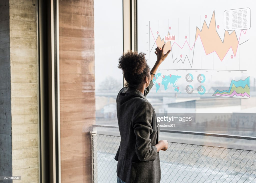 Young woman touching windowpane with graph in office : Stock Photo